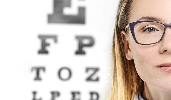una ragazza con degli occhiali da vista e dietro un pannello con le lettere dell'alfabeto scritte