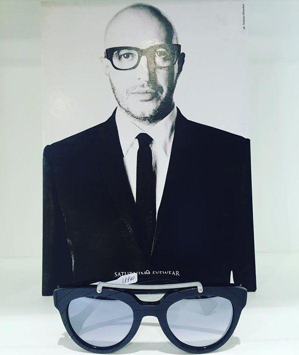 un paio di occhiali da vista e dietro la foto di un uomo che li indossa