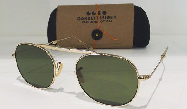 degli occhiali da sole e dietro una custodia con scritto Garretti Leight