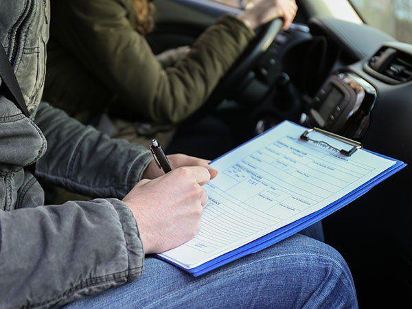 un uomo dentro a un'auto sta scrivendo sul rilievo di scrittura e accanto un altro sta guidando