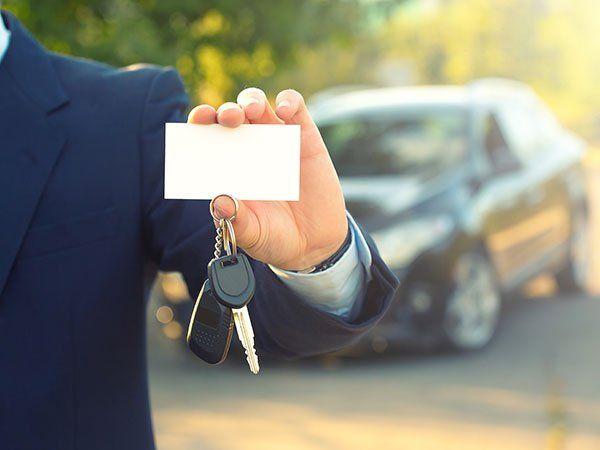 un uomo che mostra con la mano una targhetta bianca con un portachiavi e una chiave appesa