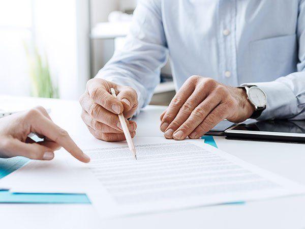 un uomo con in mano una matita che indica un foglio e dall'altra parte un'altra mano che indica il foglio con il dito indice