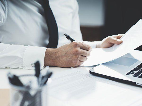 un uomo alla scrivania con in mano una penna e un foglio