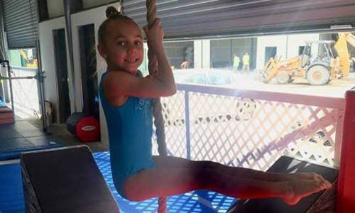 Young gymnast hanging on a rope