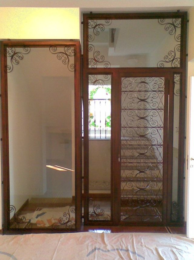 una porta e una finestra con dei pannelli di vetro e dei disegni in ferro battuto
