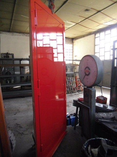 una porta in metallo di color rosso in un magazzino