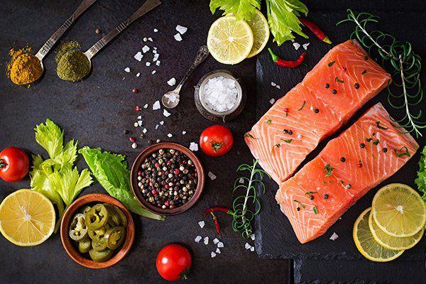 cucchiai con spezie,foglie di insalata, pomodori, sale,peperoncino e due filetti di salmone con pepe nero,bianco e verde