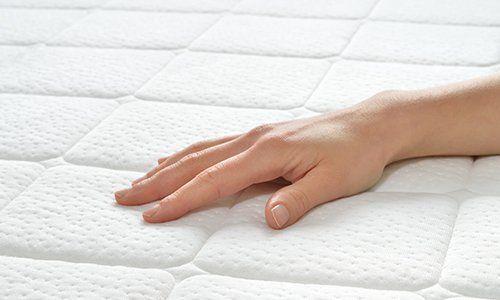 una mano appoggiata su un materasso