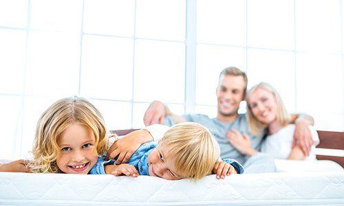 dei bambini sdraiati su un materasso e dietro una coppia abbracciata
