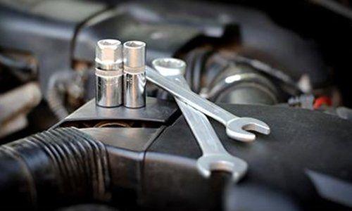 due chiavi inglese appoggiate su un motore di una macchina