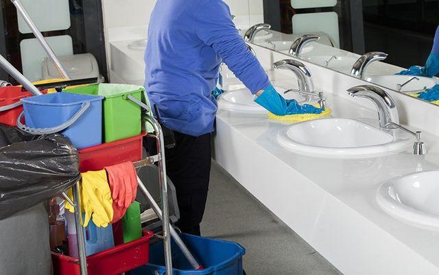 un inserviente che pulisce dei lavabi in un bagno e dietro un carrello con un kit da pulizia