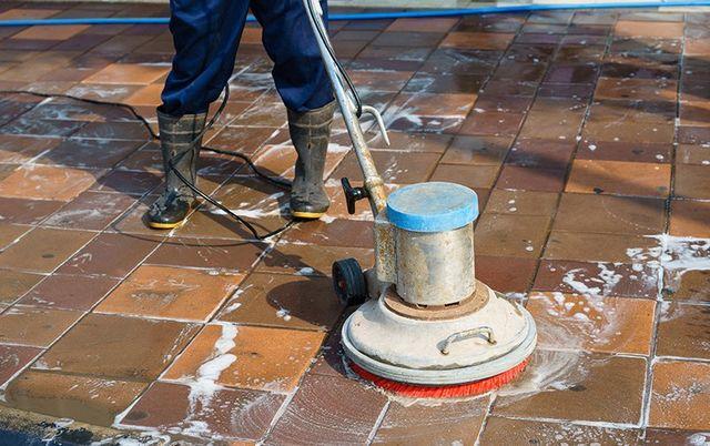 un uomo con degli stivali mentre usa una monospazzola su un pavimento