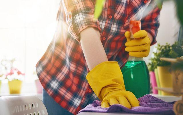 un uomo con una camicia rossa a scacchi con dei guanti gialli, uno straccio e uno spruzzino in mano mentre pulisce un tavolo