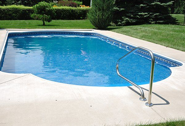Classica piscina circondata da pavimento di pietra e l'erba