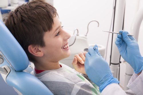 A child in a dentist chair, smiling