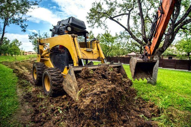 Mini bulldozer giallo che lavora la terra