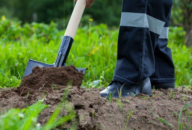 Coltivatore che scava in un giardino