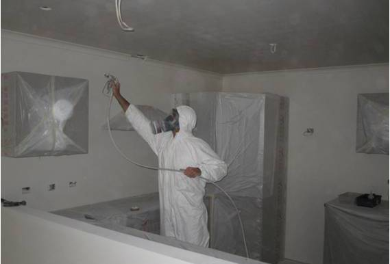 Wayne Webb Painter airless spray painting ceiling and walls in a residential house in Northland