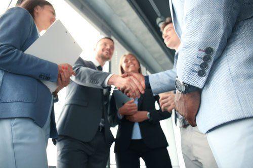 un gruppo di persone di cui due che si stringono la mano