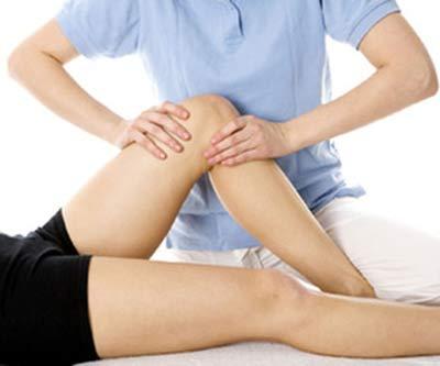 due mani che massaggiano il ginocchio di una donna sdraiata