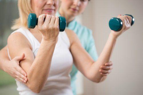 una fisioterapista che aiuta una donna che si esercita con due pesi