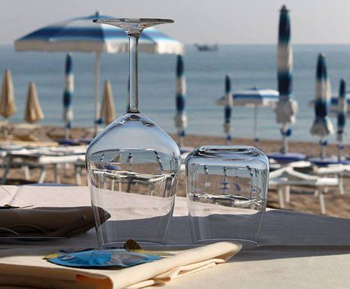 primo piano di due bicchieri su un tavolo e spiaggia sullo sfondo
