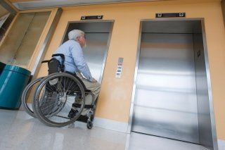 Anziano aspettando l'arrivo dell'ascensore