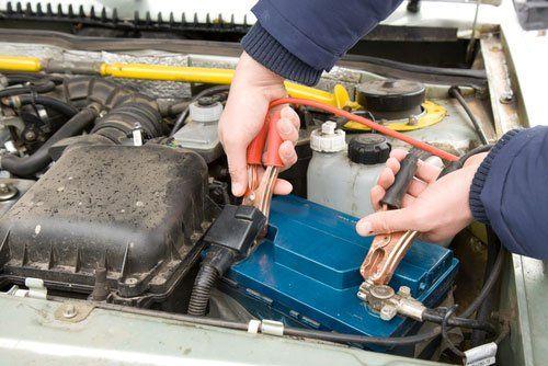 Un meccanico collega due pinze elettriche a una batteria