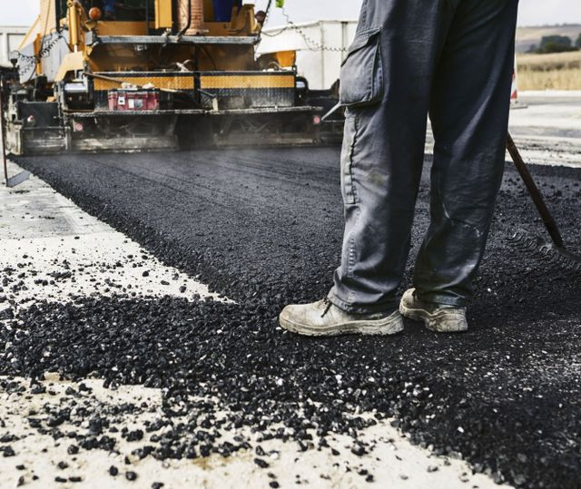 Paving contractor applying asphalt work