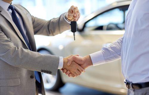 una stretta di mano e la consegna delle chiavi di una vettura