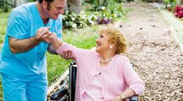 un infermiere che tiene per mano una donna anziana su una sedia a rotelle