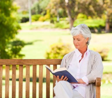 una signora seduta su una panchina che legge un libro