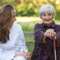 un'infermiera e una donna con un bastone sedute su una panchina
