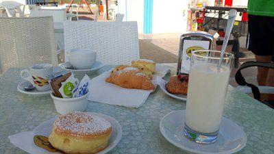 tavolo apparecchiati nel ristorante con croissant, tazze e succo