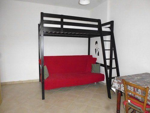 Stanza con una tavola,sedia e un letto alto con il sofá sotto