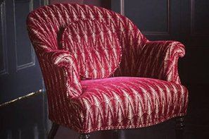 A red and white velvet tub chair with matching round cushion