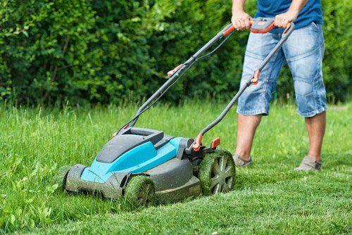operaio tosa l'erba con macchinario apposito