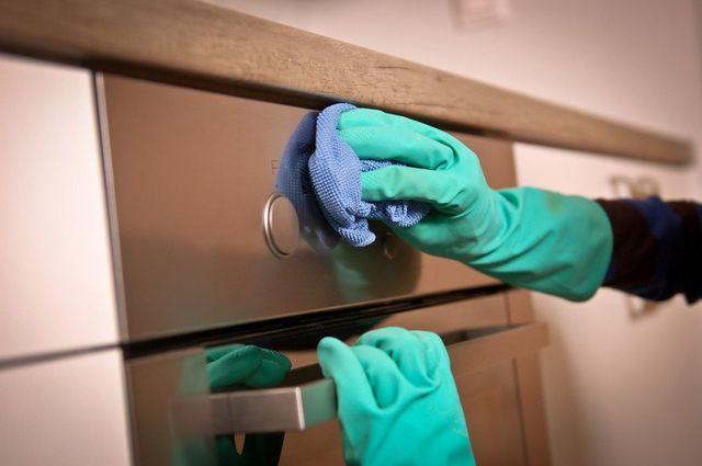 green gloved hands cleaning oven door