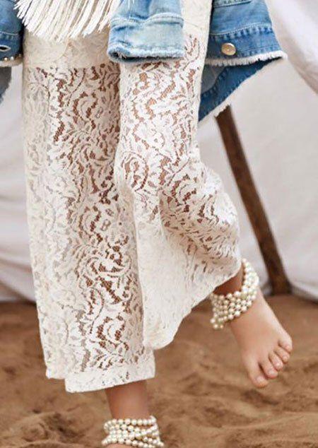Bambina di mezzo corpo indossando pantaloni bianchi di pizzo e perle sulle caviglie