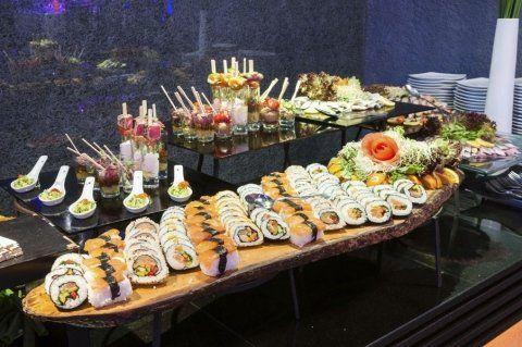 bancone con diversi vassoi di sushi, sashimi e finger food