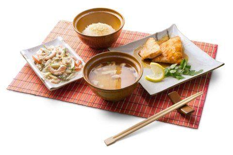 ciotola di miso, due vassoi di pesce e una ciotola di riso