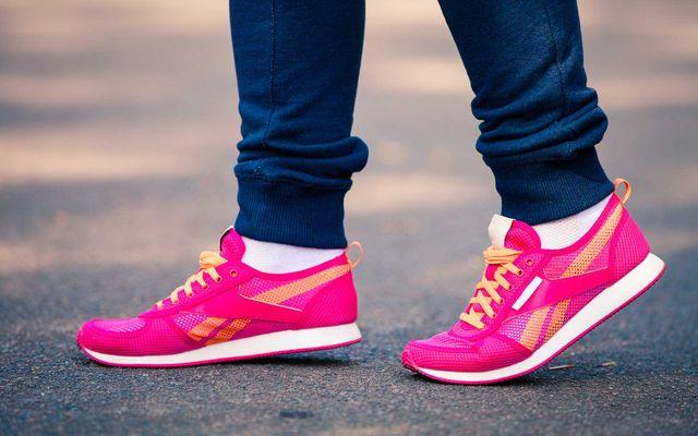 Ragazza giovane indossa circa sportive rose con orla e cordoni di colore arancio