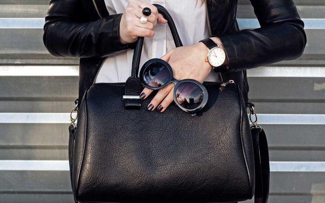 Signora subordinando una borsa di pelle nera, un paio di occhiali da sole oscure e luce orologio d'oro e anello di duplice perla nera e bianca