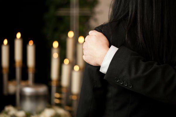 una persona che conforta una donna durante un rito funebre