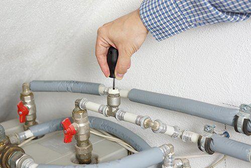 operaio lavora su un impianto termoidraulico