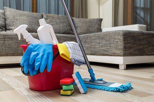 Secchio rosso con prodotti di pulizia in una casa