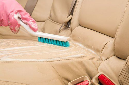 mano che pulisce il sedile di una macchina