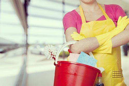 Donna con  un secchio rosso con prodotti di pulizia