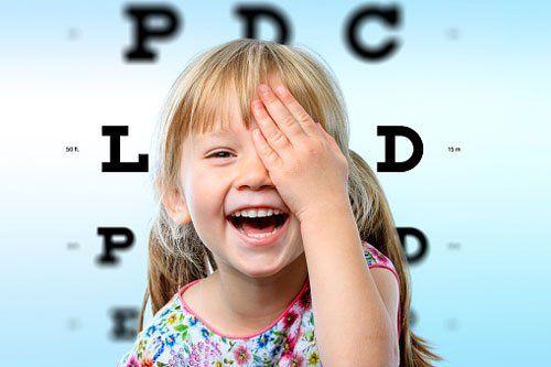 bambina che ride coprendosi l'occhio sinistro