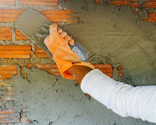 cementando un muro di mattoni